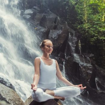 Young woman doing yoga at waterfall